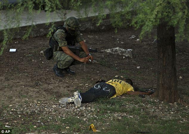 Żołnierz robi zdjęcie zabitemu członkowi kartelu